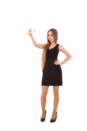 vestido corto: girl in a black short dress on a white background. girl photographing Selfe Foto de archivo