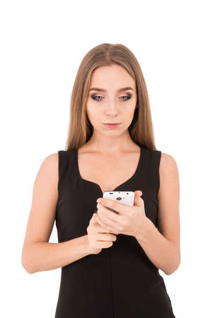 wonderment: girl in a black dress on a white background. girl reads and writes sms