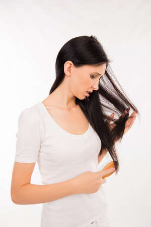 young brunette woman brushing her hair and disappointing condition her hair Stock Photo