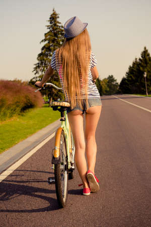 back of sexy shapely girl with hat and mini shorts walking with bicycle
