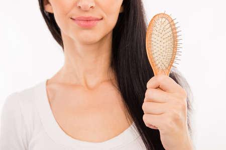 hairbrush: Happy cute young woman holding hairbrush