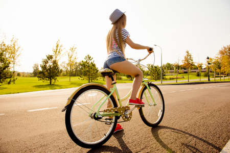 girl in shorts: sexy shapely girl with hat and mini shorts ride a bicycle