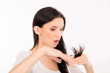 shoked: shoked young woman cutting her split ends