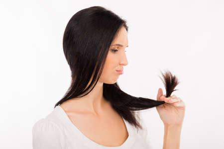 split ends: Sad young woman looking at split ends of her damaged long hair
