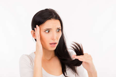 damaged: shocked girl looking at her damaged ends of hair Stock Photo