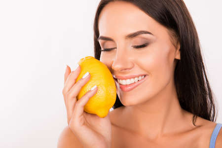 holding close: sexy beautiful young woman sniffing the scent of lemon
