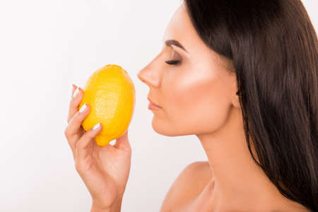 skin care: sexy beautiful young standing in profil woman sniffing the scent of lemon