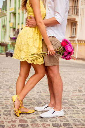 hugging legs: legs of loving hugging couples on the pavement with flowers