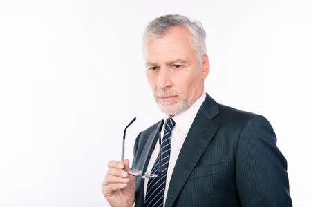 ponder: handsome intelligent  old man in business suit  holding glasses and ponder