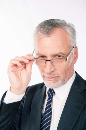to ponder: handsome intelligent  old man in business suit  holding glasses and ponder