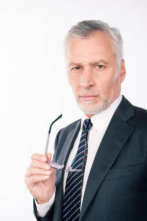ponder: handsome intelligent  old businessman holding glasses and ponder