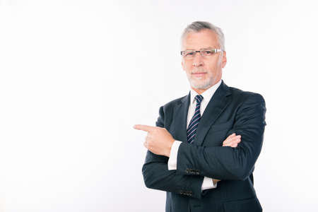 intelligent: confident intelligent  businessman with gray beard and glasses pointing aside Stock Photo