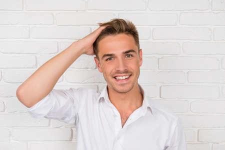 hombres jovenes: joven mostrando su cabello saludable y sonriente Foto de archivo