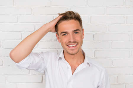 young business: young man showing his healthy hair and smiling