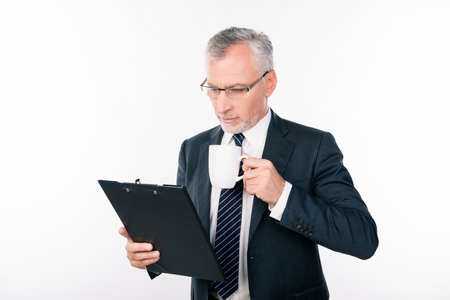 businessman pondering documents: old confident businessman with glasses reading information in a folder holding a cup