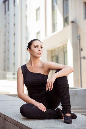 ballerina girl: Graceful attractive ballerina sitting on the balusters