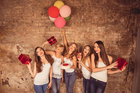 hen party: Happy pretty girls holding birthday cake, balloons and presents
