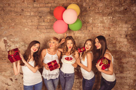 hen party: Funny pretty girls holding birthday cake, balloons and presents