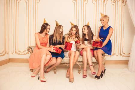 despedida de soltera: Las muchachas hermosas celebran cumplea�os sentado en el sof�