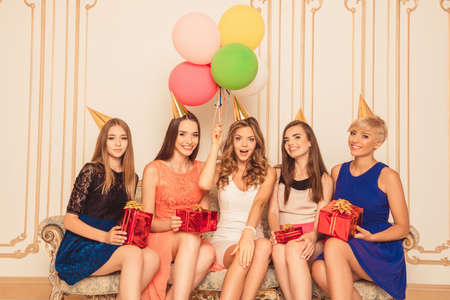 sitting pretty: Pretty girls with balloons holding birthday presents sitting on the sofa