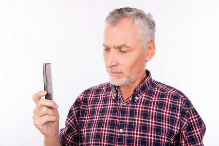 disturbed: Disturbed aged man holding a comb