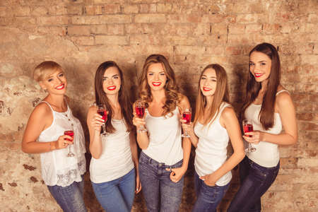 dress code: Cheerful young women wearing dress code celebrating with sparkling wine