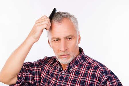Upset gray aged man combing his  hair