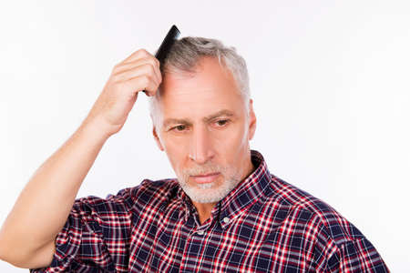 Upset gray aged man combing his  hair