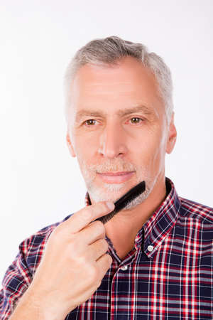combing: Confident aged man combing his beard Stock Photo