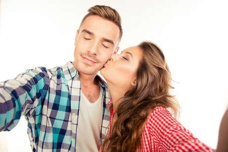 Happy pretty girl kissing her boyfriend making selfie