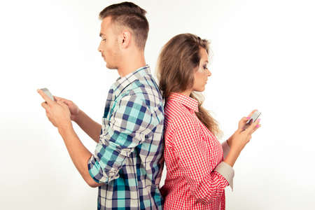telephones: Couple in love ignoring each other with telephones