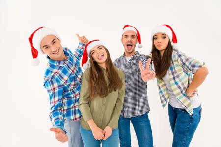 sombrero: Grupo de jóvenes divertidos en sombreros de santa celebrando navidad