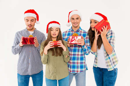 wondered: Young wondered people in santa hats holding presents