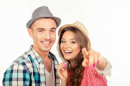 wonder woman: Cheerful pretty couple in love with hats pointing the camera Stock Photo