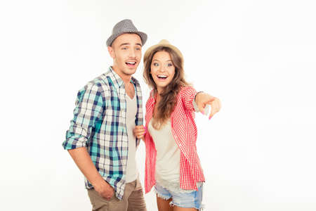 Cheerful pretty couple in love with hats pointing away Stock fotó
