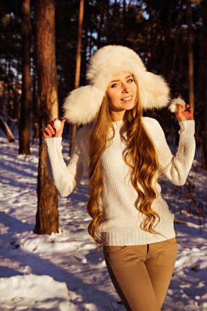 white fur: Cheerful pretty girl holding white fur hat in winter forest