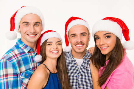 smiling faces: Portrait of happy young people in santa hats
