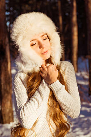 shutting: Happy cute girl wearing white fur hat in winter forest shutting her eyes