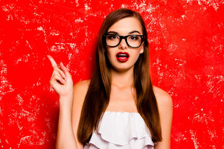 sexual: Pretty girl with glasses pointing away against the red background