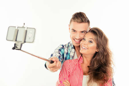 making fun: Happy cute couple in love making selfie photo with selfie stick Stock Photo