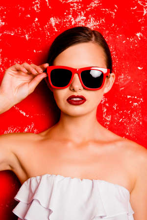 pomatum: Cute girl holding the spectacles against the red background Stock Photo