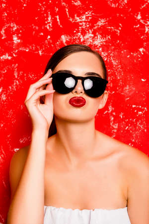 pomatum: Fashionable funny girl holding the glasses against the red background