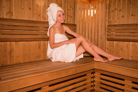 vaporarium: Beautiful girl in towel sitting on the bench in sauna