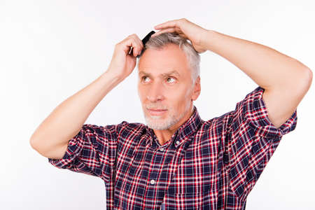 Confident gray aged man combing hair