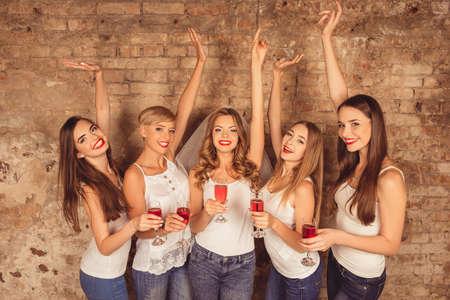despedida de soltera: Novia alegre y damas de honor felices celebrando la gallina-partido con champ�n rojo Foto de archivo