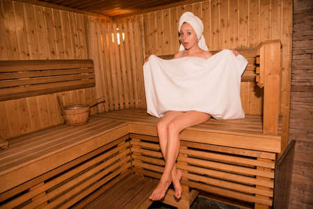 Surprised girl in towel sitting on the bench in sauna Фото со стока