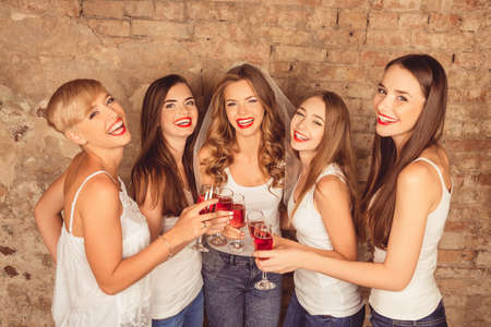red hen: Attractive bride and happy bridesmaids celebrating hen-party with red champagne