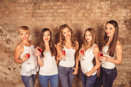 dress code: Cute young women wearing dress code celebrating with sparkling wine