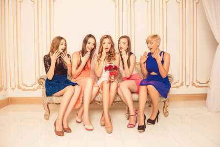 chic woman: Pretty surprised bride with girlfriends sitting on the sofa Stock Photo