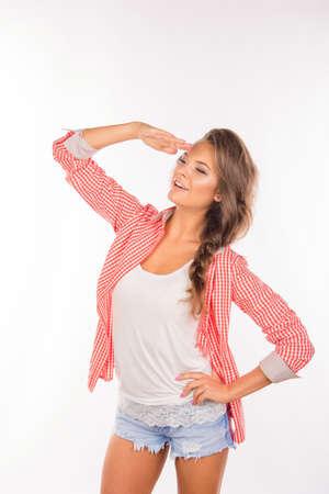 saluting: Beautiful cheerful girl saluting like a soldier